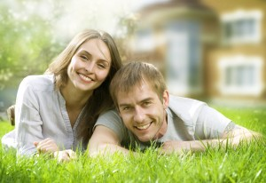 Happy Couple Near Their Home. Smiling Family Outdoor. Real Estate
