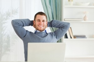 Smiling young businessman leaning back in his homeoffice