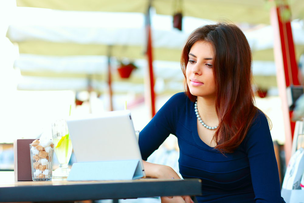 Elegant beautiful woman with tablet computer drinking coffee at cafe